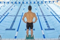 飛び込み台に立つ男子水泳選手