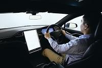 自動運転の車を運転する日本人男性