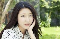 緑のある庭で見つめる20代日本人女性