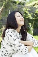 緑のある庭で微笑む20代日本人女性