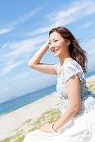 芝生に座って髪に触れる日本人女性