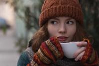 カプチーノを飲むニット帽の女性