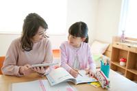 子供部屋で先生に勉強を教わる女の子