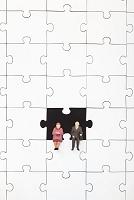 ジグソーパズルの隙間に座る人形