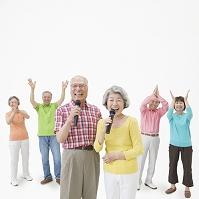 マイクを持って歌う男女と拍手するシニア男女達