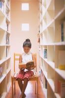本棚の前で本を読む女の子