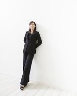 壁にもたれて立つスーツ姿の女性