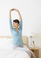 ベッドで伸びをするシニアの女性