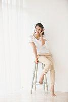 ハイチェアに腰掛け電話する日本人女性