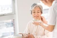 シニア日本人女性患者の食事介助をする介護士