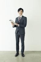 タブレットを使うスーツの20代の男性