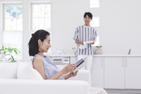 ソファに座って読書する女性とキッチンでお皿を拭く男性