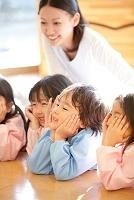頬杖の日本人の子供と保育士