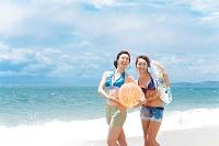 波打ち際でビーチボールと浮き輪を持っている日本人女性