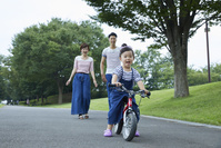 キックバイクに乗る女の子と見守る両親