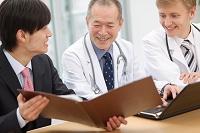 医師に資料を見せるビジネスマン