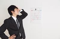 カレンダーと落ち込むビジネスマン