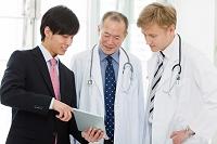 医師にタブレットを見せるビジネスマン