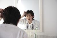 鏡を見て髪が気になる男性