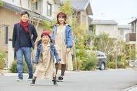 家の前に並ぶ家族