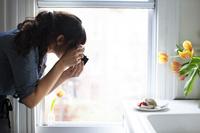 窓辺でお菓子の写真を撮る女性