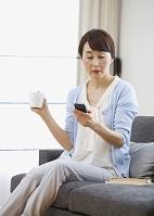 ソファに座ってスマホを操作するシニアの日本人女性