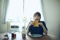 部屋で朝食を食べる日本人女性