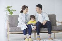 スマートフォンを見る息子と見つめ合う両親