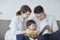 息子にiPadを見せる両親