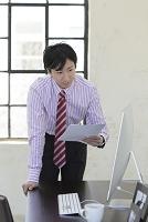 明るいオフィスで働く日本人ビジネスマン
