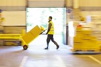 倉庫で荷物を運ぶ外国人男性作業員