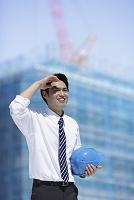 建築現場でヘルメットを持つスーツ姿の男性