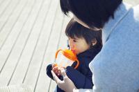 屋外に座り飲み物を飲む男の子