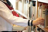本を取ろうとしている女子高校生