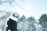 冬の林と見上げるニット帽子の日本人女性