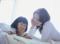 寝室のベッドでくつろぐお母さんと女の子