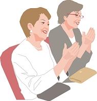 劇場で拍手するアクティブシニアの女性