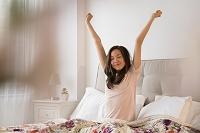 ベッドで伸びをするハーフの女性