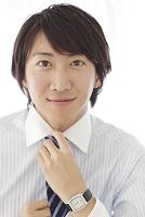 出勤前にネクタイを整える日本人ビジネスマン