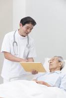 在宅医療する医者とシニア男性患者