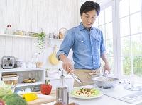 料理を盛り付ける日本人男性