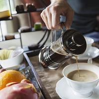 カップにコーヒーを注ぐ男性