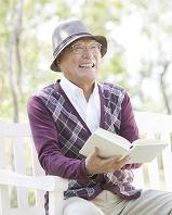 ベンチに座って本を読むシニアの日本人男性