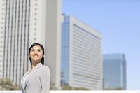 ビル街に立つ日本人ビジネスウーマン