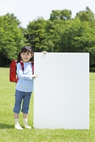 新緑の中ホワイトボードを持つランドセルの女の子