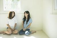 床に座り会話する20代日本人女性