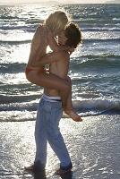 海辺でキスをする若いカップル