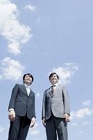 青空の下に立つ日本人ビジネスマン