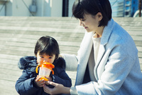屋外に座り飲み物を飲む男の子と見守る母親
