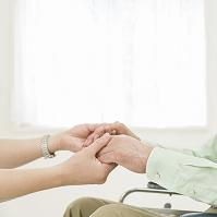 患者の手を握る看護師